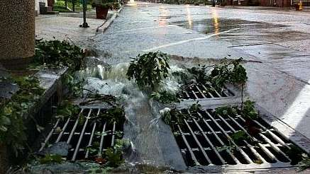 Water floods into a drain in Northport during