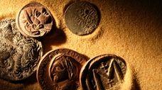 Few ancient coins on sand background under beam