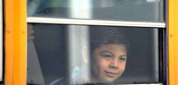 A kindergartner looks out the window of a