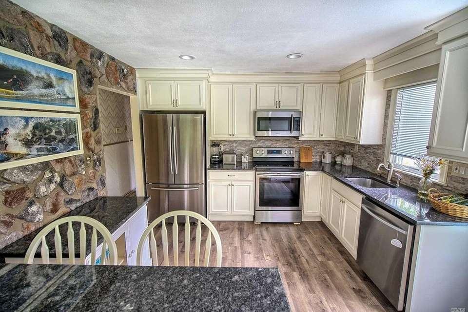 The kitchen features granite countertops, stainless steel appliances