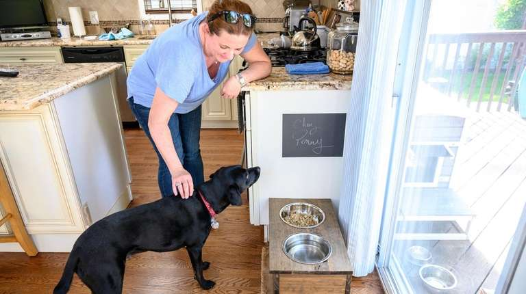 Karla Modolo feeds her dog, Penny, at their