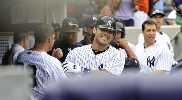 Jesus Montero smiles in the Yankee dugout after