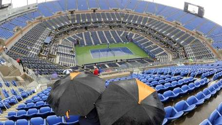 Tennis fans sit in the rain in the