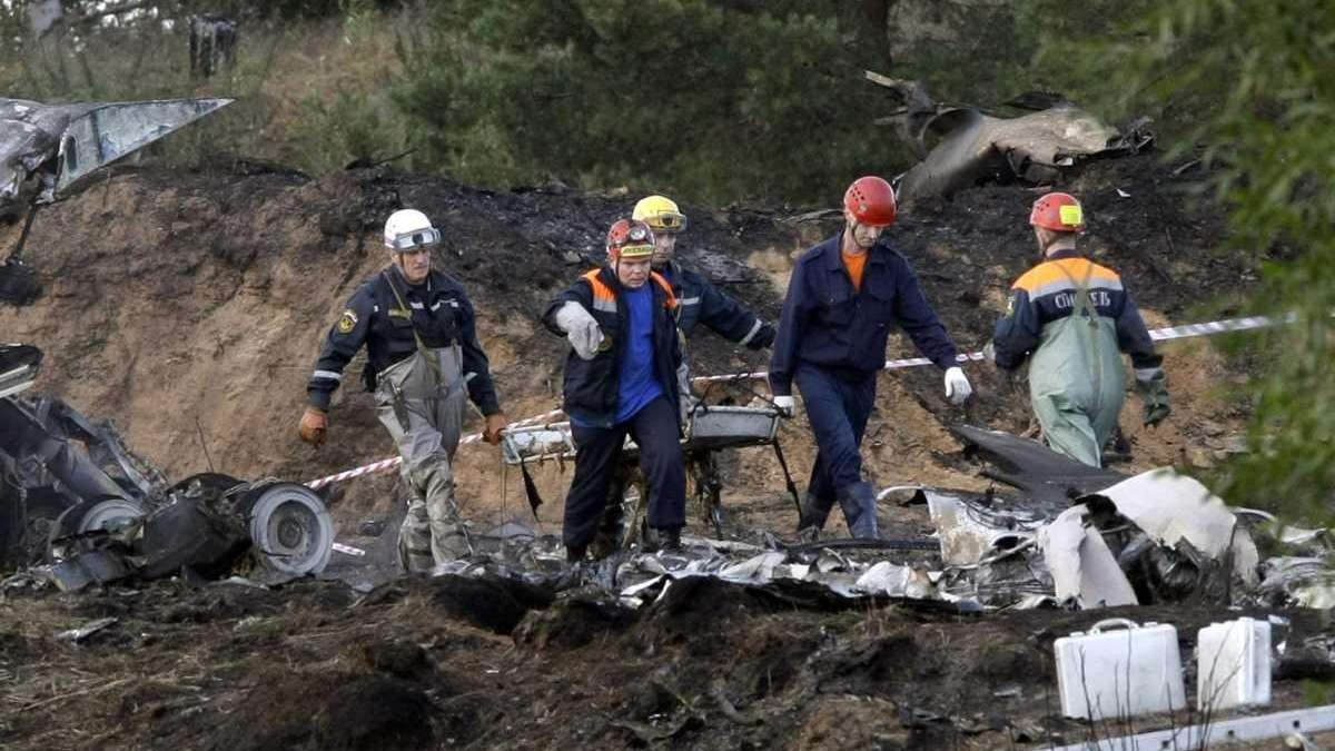 Rescuers carry a stretcher with the body of