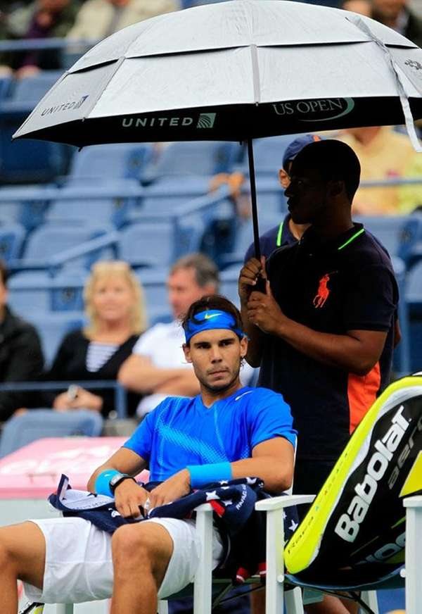 Rafael Nadal of Spain sits under an umbrella
