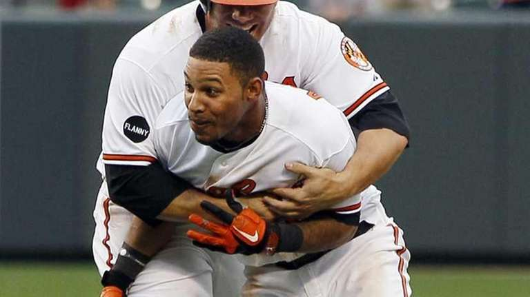 Baltimore Orioles' Robert Andino, front, is embraced by