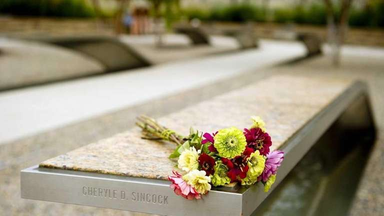 Flowers rest on a bench as visitors to