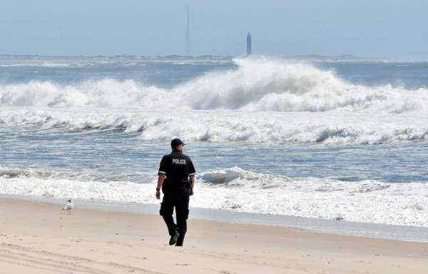 A Suffolk County marine police officer walks Gilgo