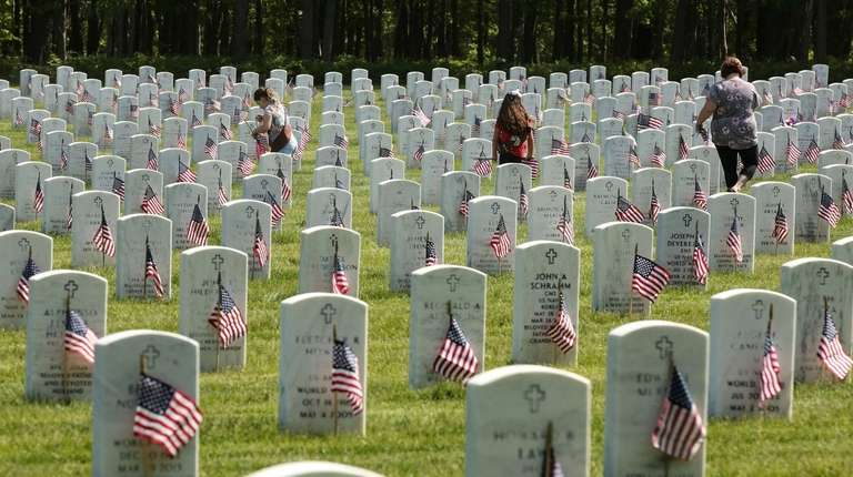 Volunteers place American flags on the graves of