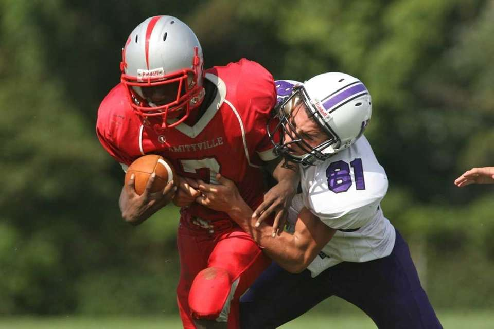 Amityville's quarterback Sean Walters is tackled by Port