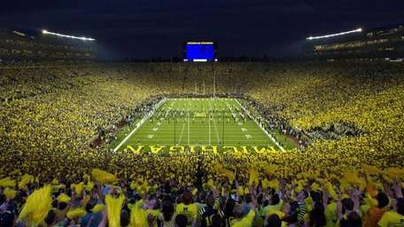 Michigan fans wave pom-poms before an NCAA college