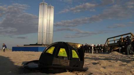 A firefighter's hat lays in the sand near