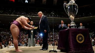 "President Donald Trump presents the ""President's Cup"" to"