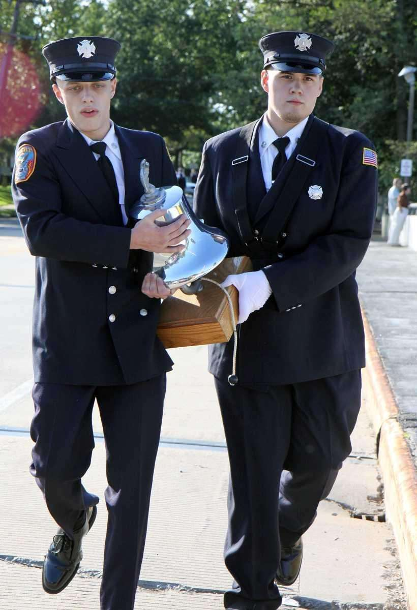 Firefighters carry a bell used in the 9/11