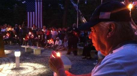 Charles Raynor, of Shoreham, holds a candle during