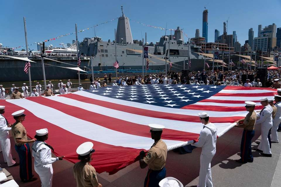 Soldiers, sailors and marines unfurl a 100-foot American