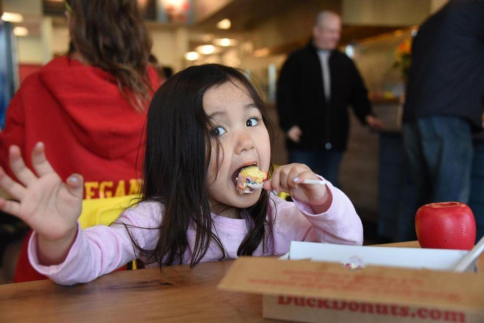 Chloe Bronzino, 3, of Smithtown, takes a bite