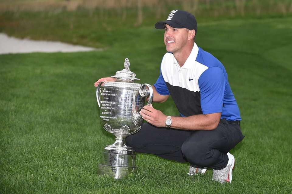Brooks Koepka poses for pictures with trophy after