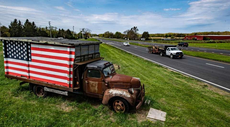 A rusted old truck with the American flag