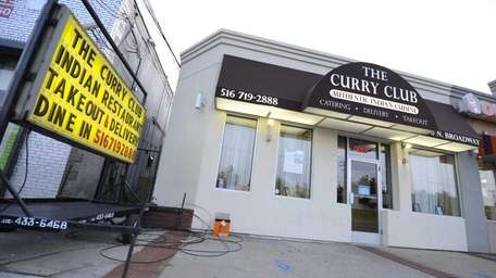 A sign is displayed outside Curry Club in