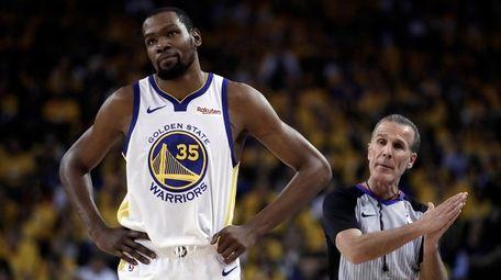 Golden State Warriors' Kevin Durant, left, walks away