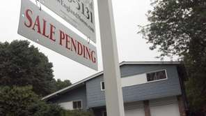 A sign announces a pending residential home sale