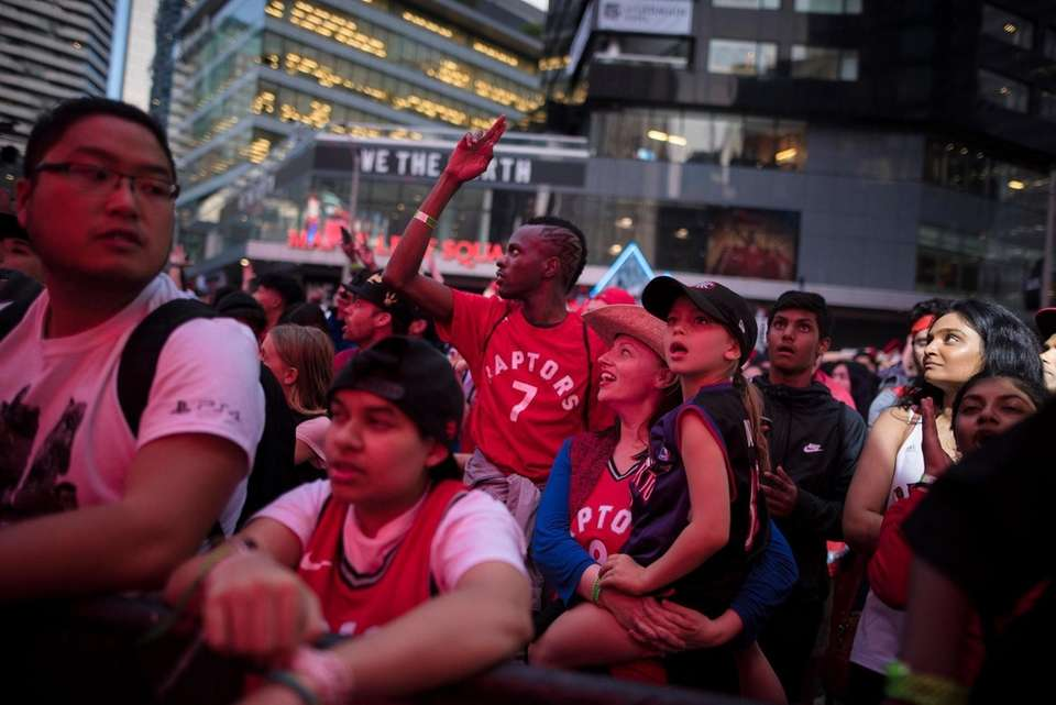 Toronto Raptors fans cheer outside Scotiabank Arena, at