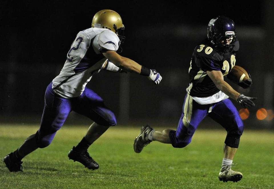 Islip's Johnny Maher gains yardage ahead of a