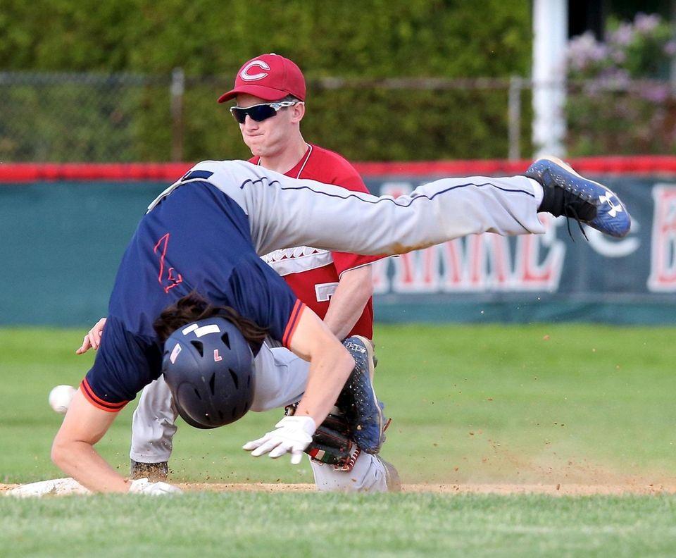 Manhasset's Jay Schlaefer trips over Clarke second baseman