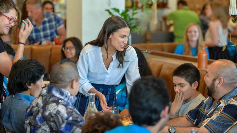 Ocasio-Cortez mingles as she delivers food.