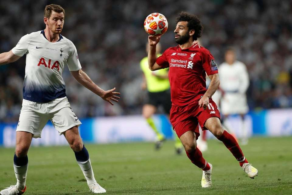 Liverpool's Mohamed Salah, right, challenges for the ball