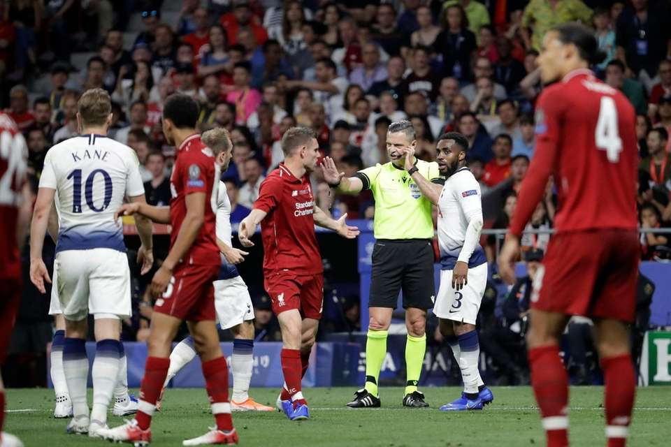 Liverpool's James Milner, center left, argues with Referee