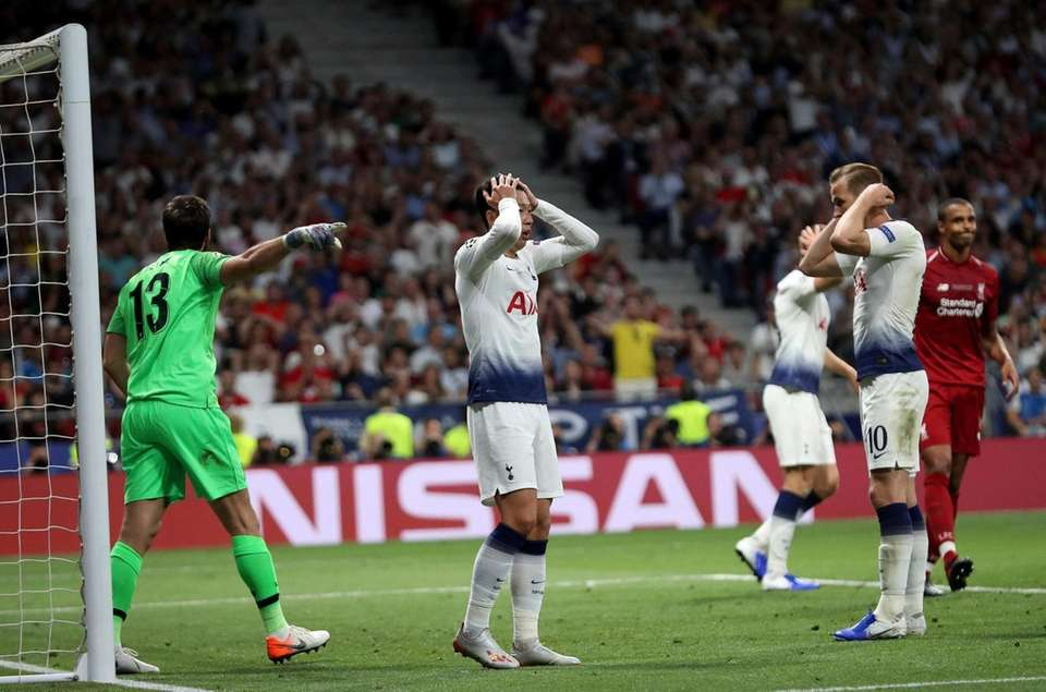 Tottenham's Son Heung-min, center, holds his head after