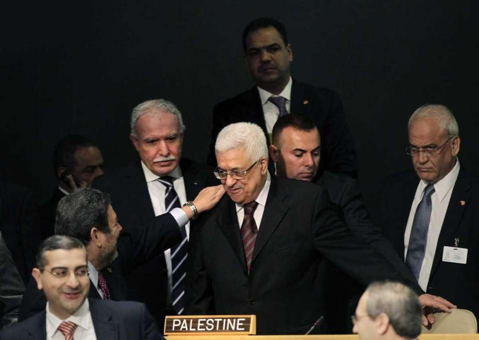 Palestinian President Mahmoud Abbas, center, is greeted before