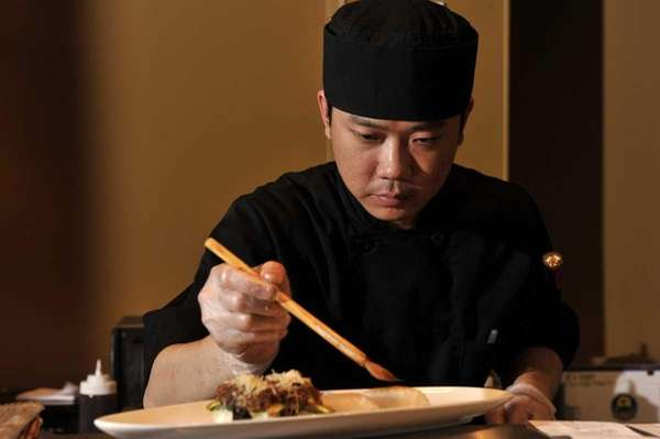Arata Sushi Chef/Owner Jimmy Lian brushes a dish