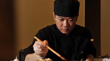 Arata Sushi Chef/Owner Jimmy Lian brushes a dish