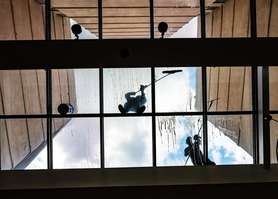 Workers clean the ceiling glass at the Marriott