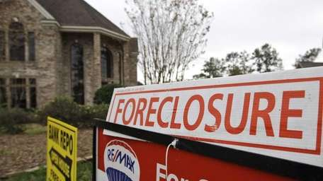 Bank-repossession and foreclosure for-sale signs hang outside a