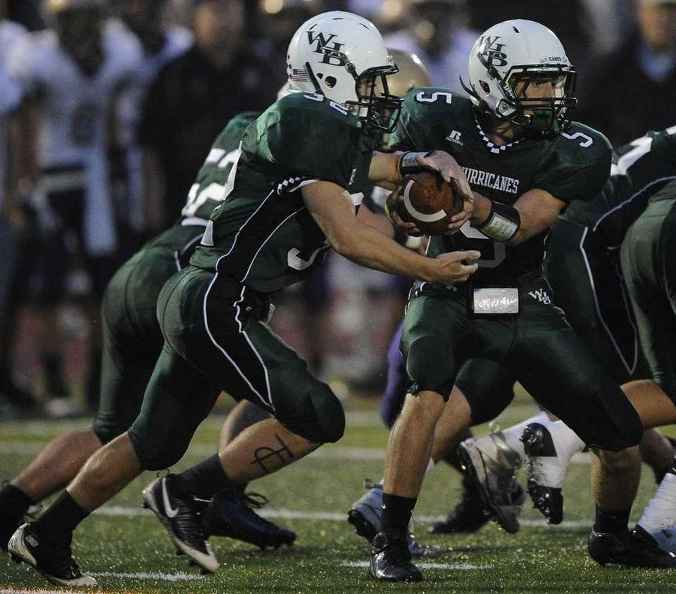 Westhampton quarterback Jack Murphy, (right), hands the ball