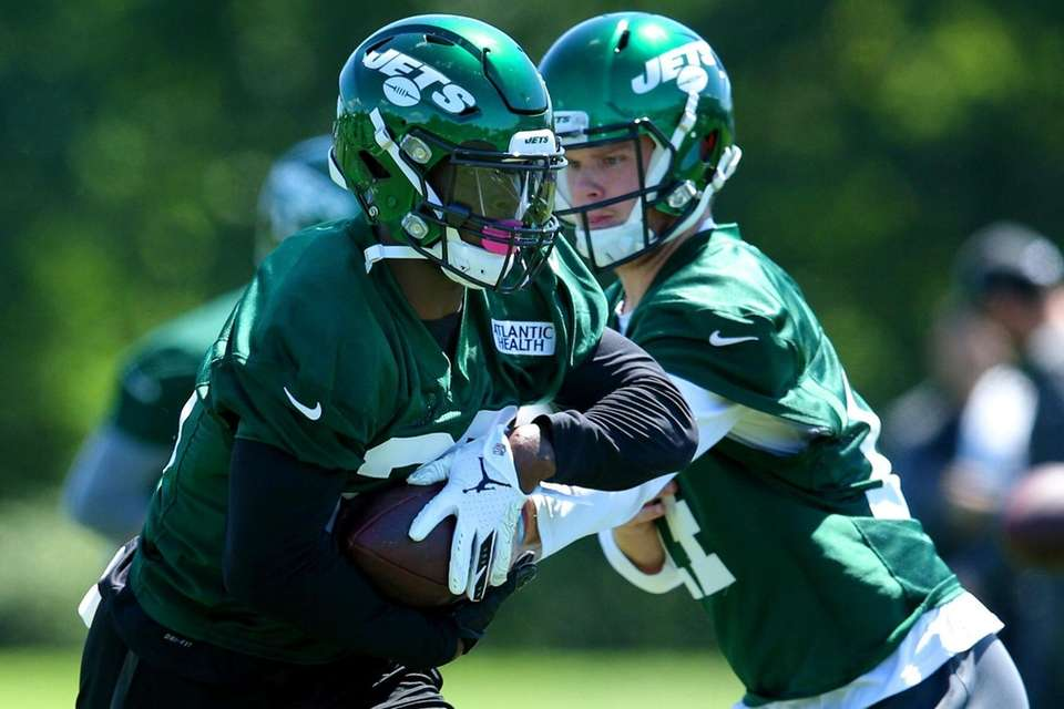 Jets quarterback Sam Darnold hands off to running
