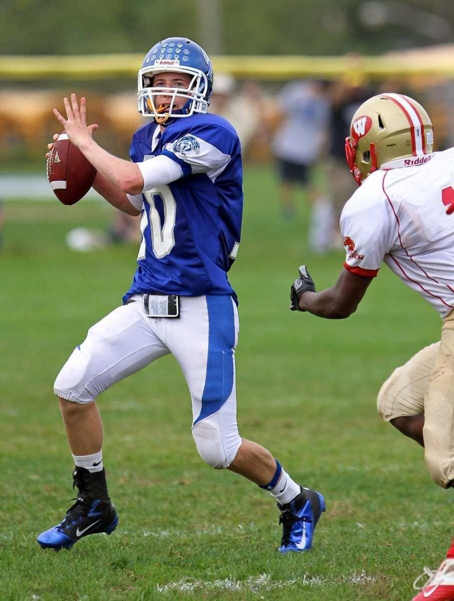 Riverhead quarterback Ryan Bitzer #10 rolls out of
