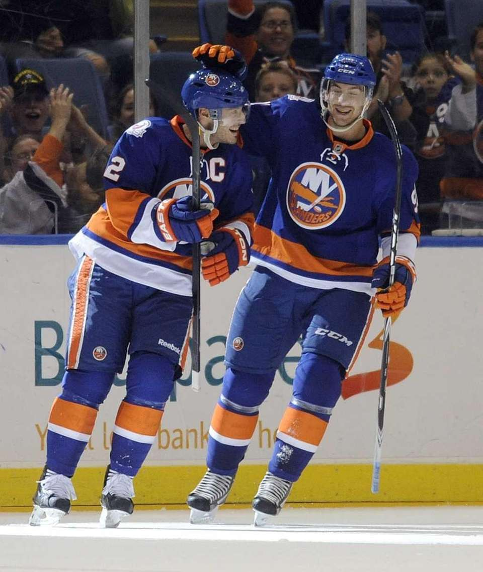 New York Islanders' Mark Streit, left, is congratulated