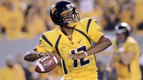 West Virginia quarterback Geno Smith drops back to