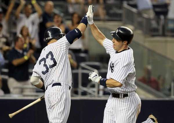 The New York Yankees' Mark Teixeira, right, celebrates