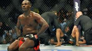 Jon Jones, left, kneels in the center of