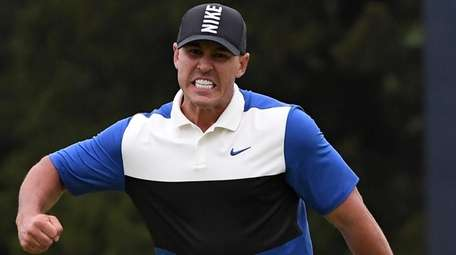 Brooks Koepka reacts after he sinks his putt