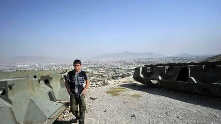 An Afghan youth walks past the remains of