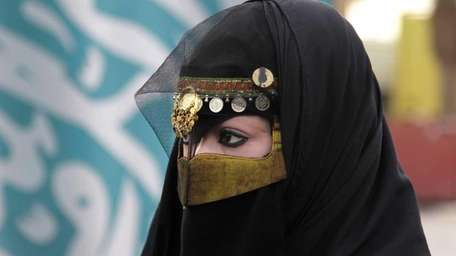 A Saudi woman attends a traditional Arda dance,