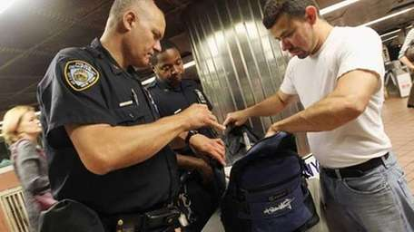 NYPD officers check bags during the morning commute