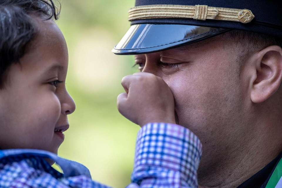 4 year-old Liam wipes away his father's tears,